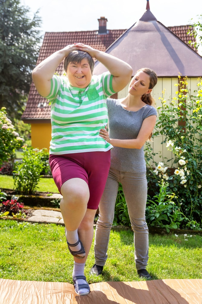 a woman with mental health problems is doing assisted exercises with support worker