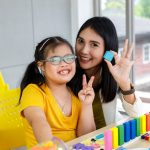 Down's syndrome learning disability teachear and kid learning together